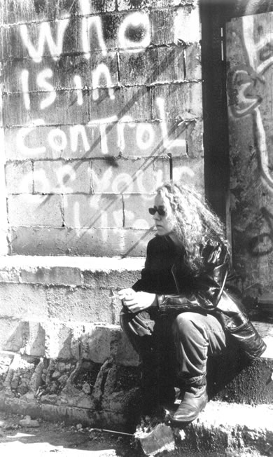 photo of Elaine sitting on steps in front of graffitti that says 'who is in control of your life'